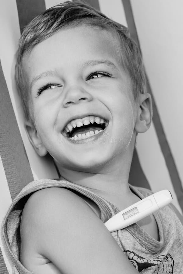 Glückliche lachende messende Temperatur des kleinen Jungen stockbild