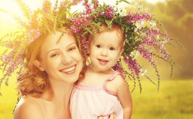 Glückliche lachende Tochter, die Mutter in den Kränzen des Sommerflusses umarmt stockbild