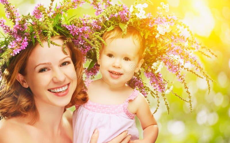 Glückliche lachende Tochter, die Mutter in den Kränzen des Sommerflusses umarmt stockfotografie