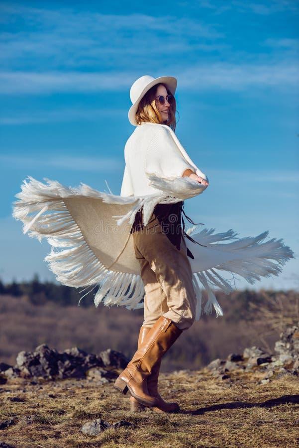 Glückliche Landfrau, die Natur in den Bergen tragen Poncho genießt stockfotos