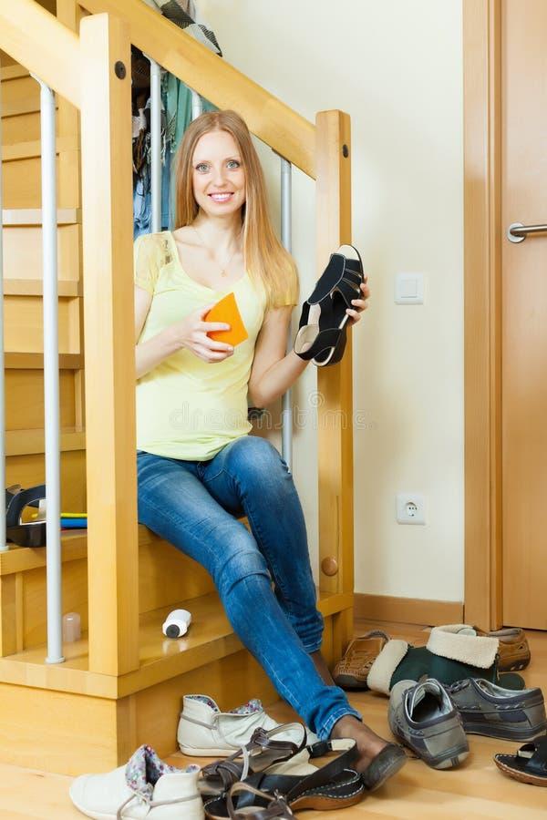 Glückliche langhaarige Hausfrau mit Schuhen lizenzfreie stockbilder