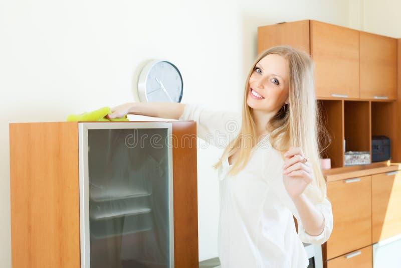 Glückliche langhaarige Hausfraureinigungsmöbel stockfotografie