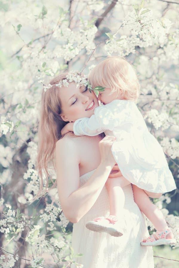 Glückliche Lebenmomente bemuttern das Umarmen des Kindes im sonnigen Frühling stockfoto