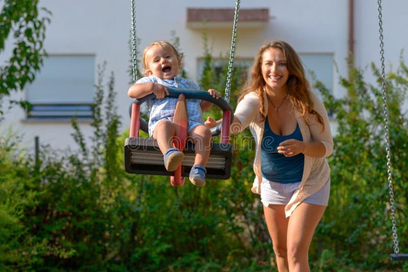 Glückliche lebhafte junge Mutter mit ihrem Babysohn lizenzfreie stockbilder