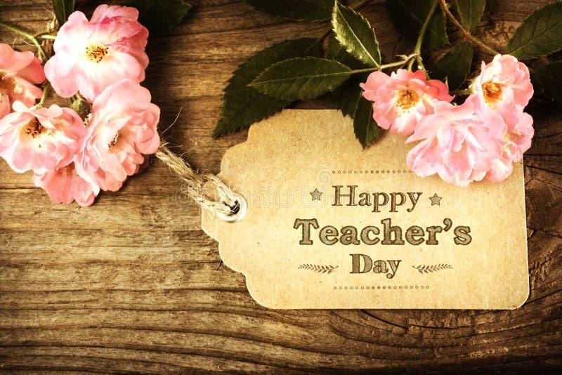 Glückliche Lehrer-Tagesmitteilung mit rosa Rosen lizenzfreies stockfoto