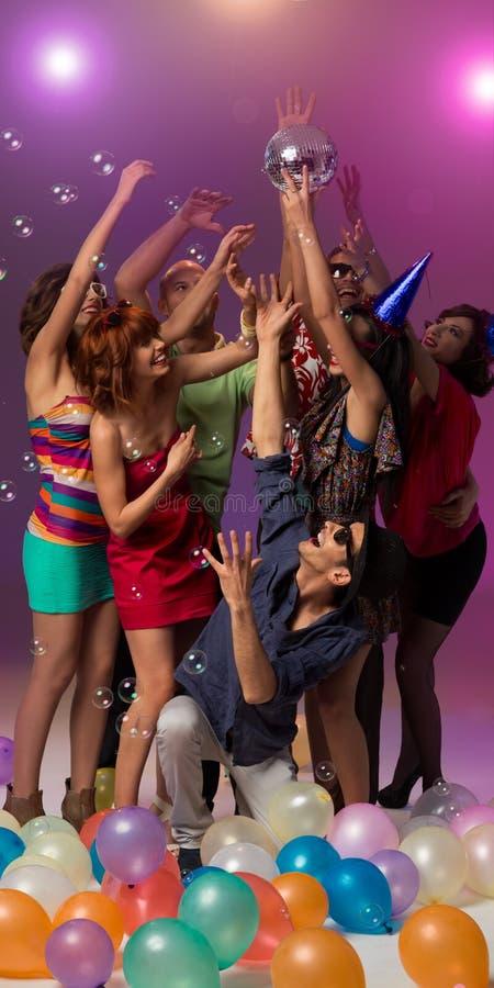Glückliche Leute an der Partei, die eine Discokugel abfängt stockfotos