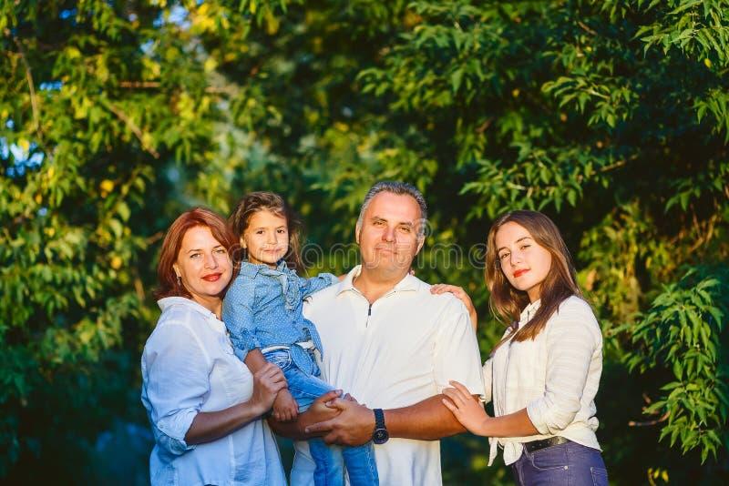 Glückliche Leute der vierköpfigen Familie im Wald auf einem Weg stockfoto