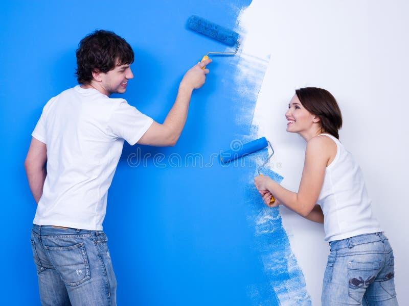 Glückliche Leute, welche die Wand auftragen stockfoto