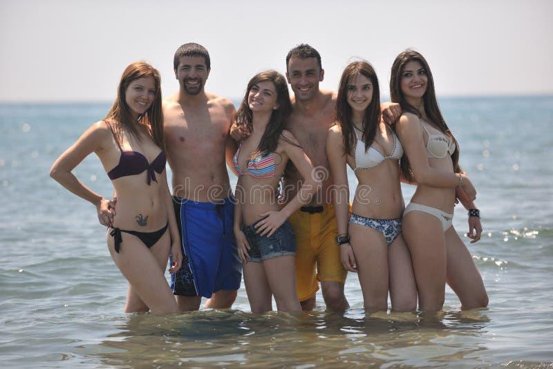 Glückliche Leutegruppe haben Spaß und Betrieb auf Strand stockfotos