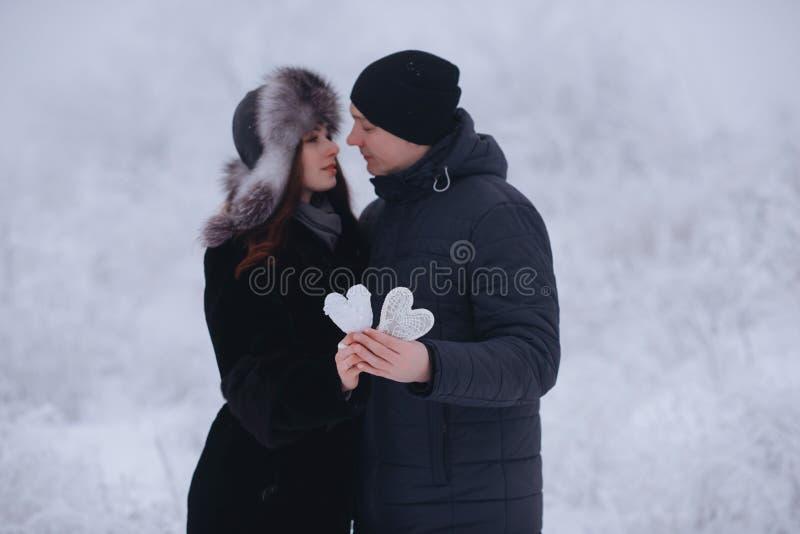 Glückliche Liebespaare im Wald im Winter-, Weg-, Kuss-, Umarmungs- und Griffpapierherzen im Park - Valentinsgruß-Tag stockbild