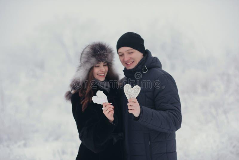 Glückliche Liebespaare im Wald im Winter-, Weg-, Kuss-, Umarmungs- und Griffpapierherzen im Park - Valentinsgruß-Tag stockfotografie