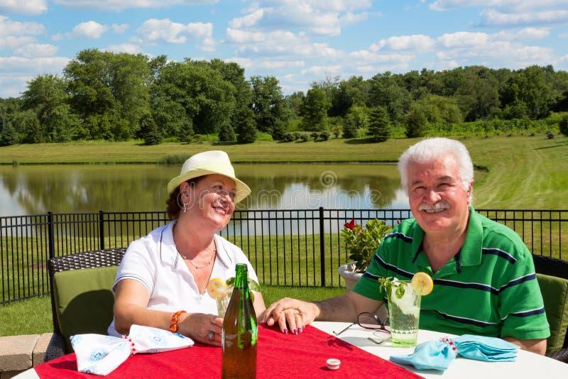 Glückliche liebevolle ältere Paare auf dem Patio stockfotos