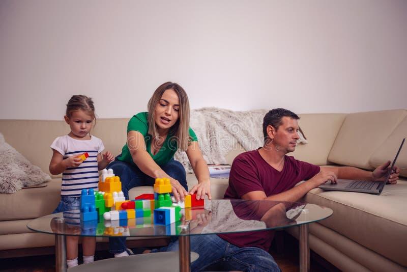Glückliche liebevolle Familie Eltern, die zu Hause mit ihrer Tochter spielen lizenzfreie stockfotografie