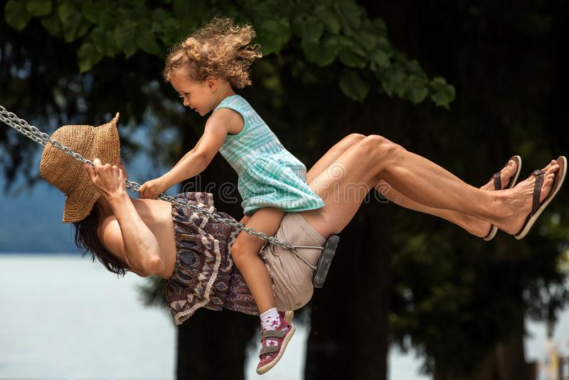 Glückliche liebevolle Familie! Junge Mutter und ihre Kindertochter, die auf dem Schwingen schwingt und draußen einen Sommerabend, stockbilder