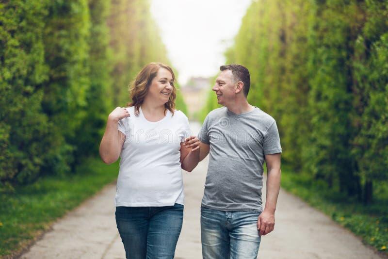 Glückliche liebevolle Paare auf einem romantischen Weg draußen im Park stockfotos