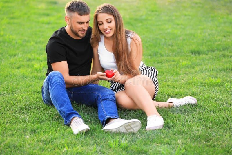 Glückliche liebevolle Paare mit dem roten Herzen, das draußen auf grünem Gras sitzt lizenzfreies stockbild