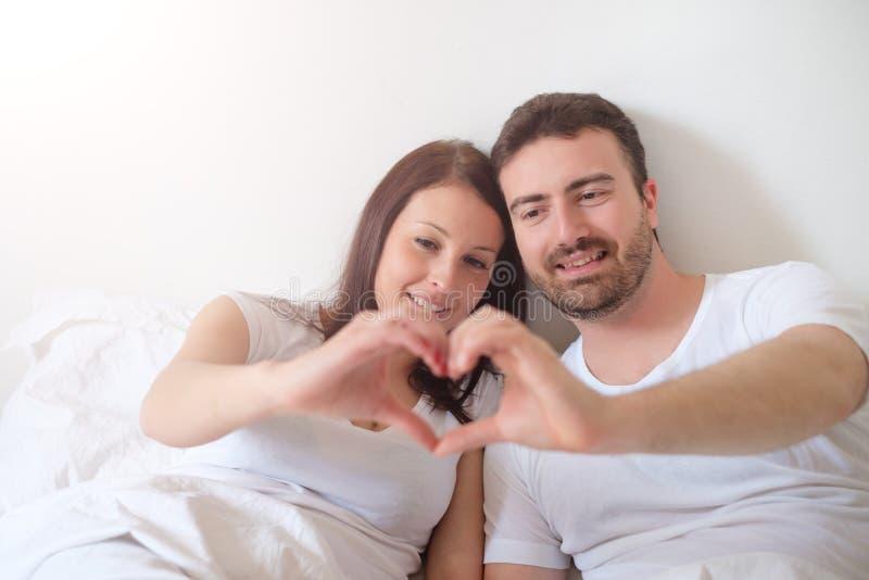 Glückliche Liebhaber verbinden das fühlende bequeme Lügen im Bett stockbilder