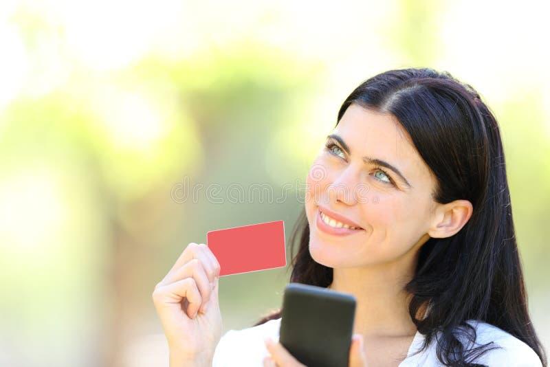 Glückliche on-line-Käufervertretungskarte und Betrachten der Seite lizenzfreie stockfotografie