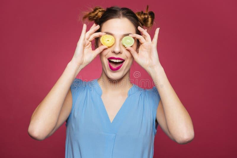 Glückliche lustige junge Frau bedeckte ihre Augen mit Marmeladensüßigkeiten lizenzfreie stockfotografie