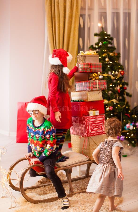 Glückliche, lustige Kinder, die sich einen Schlitten voller Weihnachtsgeschenke anziehen stockfoto