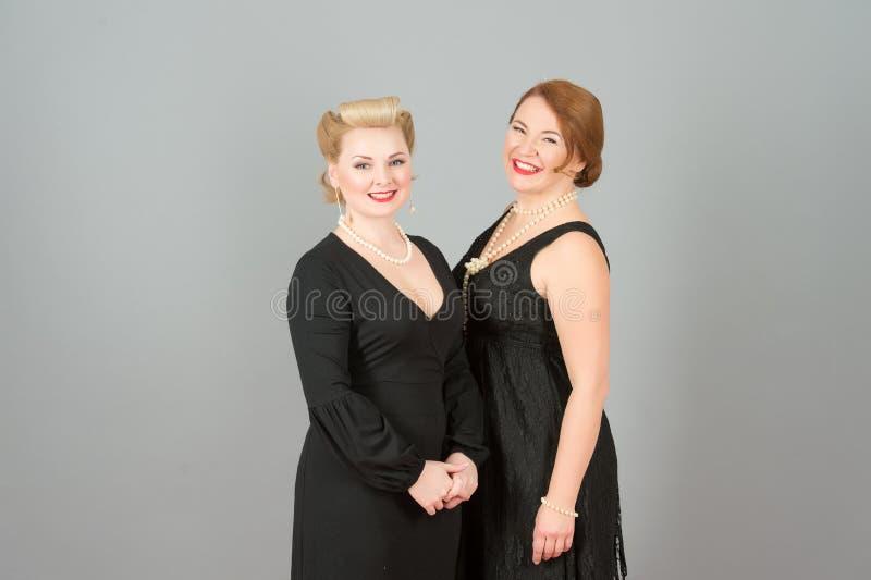 Glückliche Mädchen in den schwarzen Kleidern mit Stift-oben kräuselt Frisur auf grauem Hintergrund stockbilder