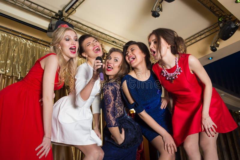 Glückliche Mädchen, die in ein Mikrofon singen stockbild