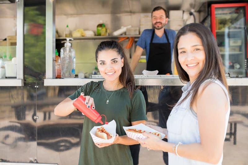 Glückliche Mädchen, die an einem Lebensmittel-LKW essen stockbilder