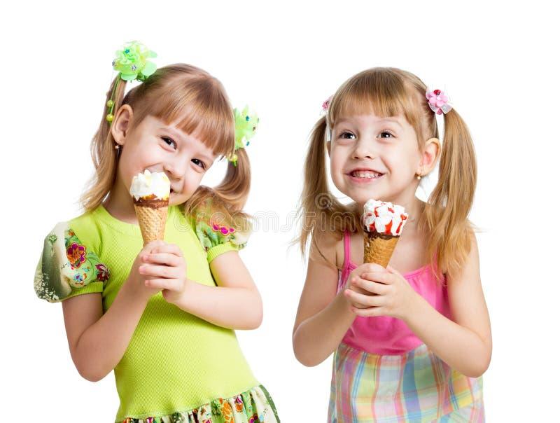 Glückliche Mädchen essen Eiscreme im lokalisierten Studio lizenzfreie stockbilder