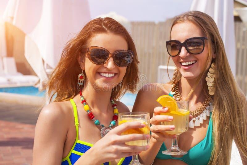 Glückliche Mädchen mit Getränken auf Sommerfest nahe dem Pool lizenzfreie stockbilder