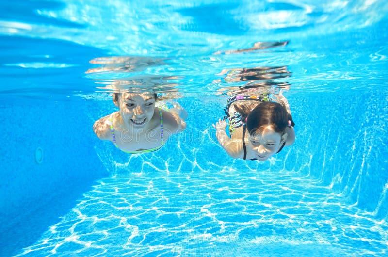 Glückliche Mädchen schwimmen unter Wasser im Pool lizenzfreie stockfotos