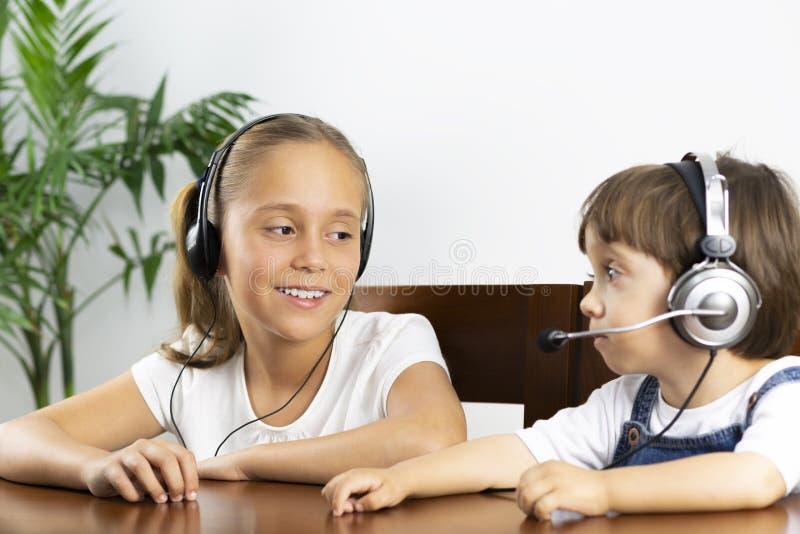 Glückliche Mädchen-und Jungen-tragende Kopfhörer lizenzfreies stockbild