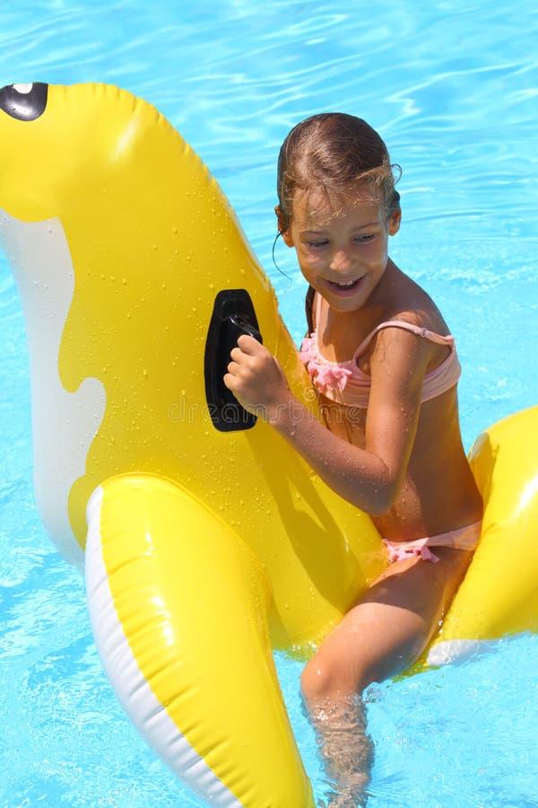 Glückliche Mädchenschwimmen am aufblasbaren Spielzeug der Kinder lizenzfreie stockfotografie