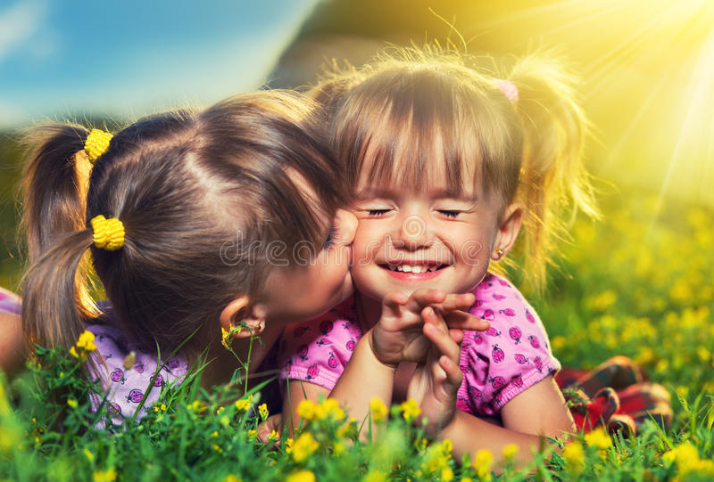 Glückliche Mädchenzwillingsschwestern, die im Sommer küssen und lachen  lizenzfreie stockfotografie