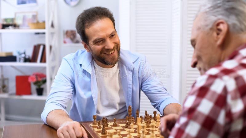 Glückliche Männer, die zu Hause Schach, Hobby und Freizeitbetätigung, Familienwettbewerb spielen stockbild