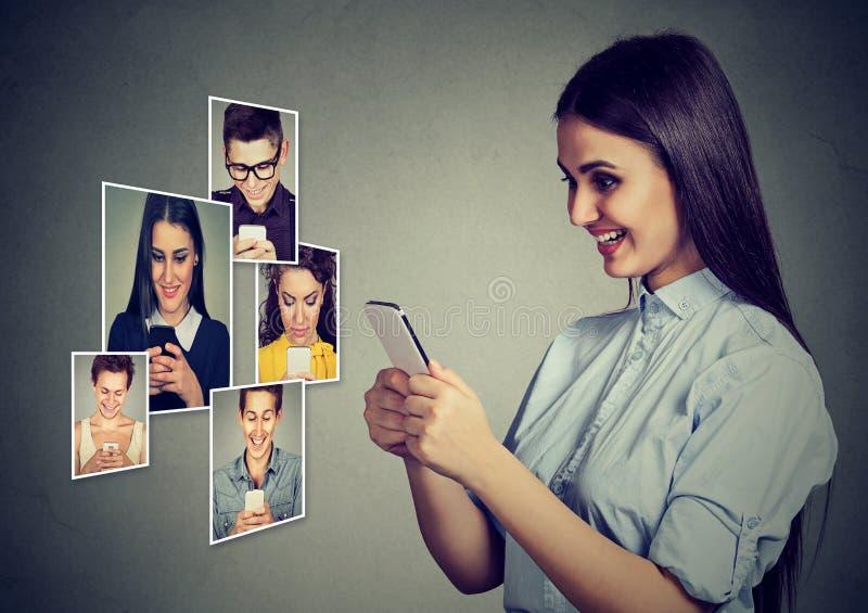 Glückliche Männer und Frauen der jungen Leute, die das bewegliche intelligente Telefonlächeln verwenden stockfoto