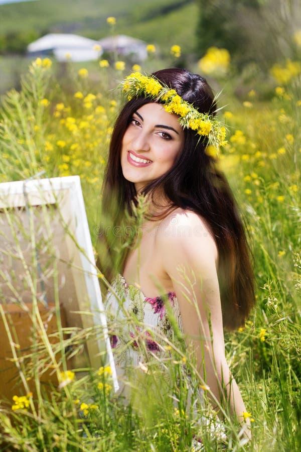 Glückliche Malerfrau ist schaffen Bild auf einem Gebiet lizenzfreies stockfoto