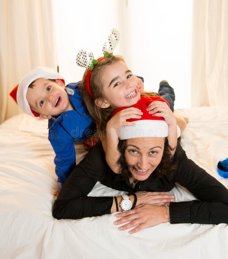 Glückliche Mama, Tochter und kleiner Sohn, die am Weihnachten spielen stockfotos