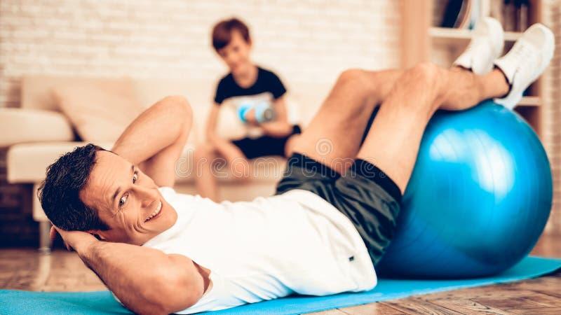 Glückliche Mann-Schwingen-Presse auf Fitball-Jungen mit Dummkopf lizenzfreie stockfotos