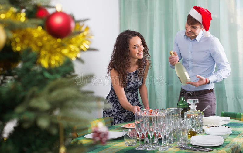 Glückliche Mann- und Mädchenumhüllung Weihnachtstabelle für Gäste stockbilder