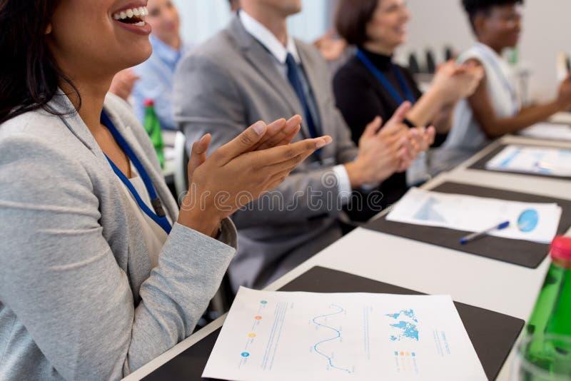 Glückliche Menschen, die bei der Geschäftskonferenz applaudieren stockfotos