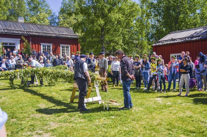 Glückliche Menschen, die genießen, um Pfostendekoration zu sehen und auf die schwedische mittlere Sommertagesfeier mit bunter Kle lizenzfreies stockbild
