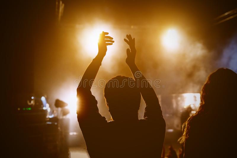 Glückliche Menschen, die Rockkonzert, angehobene oben Hände und das Klatschen des Vergnügens, aktives Nachtlebenkonzept genießen stockfoto