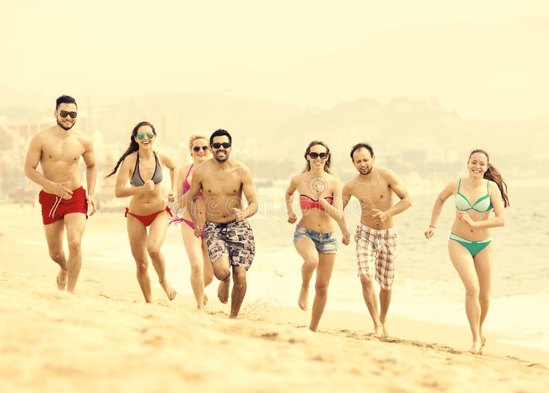 Glückliche Menschen, die am Strand laufen lizenzfreies stockbild