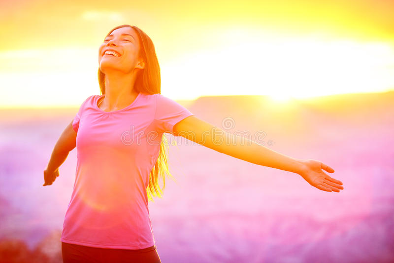 Glückliche Menschen - freie Frau, die Natursonnenuntergang genießt stockfotografie