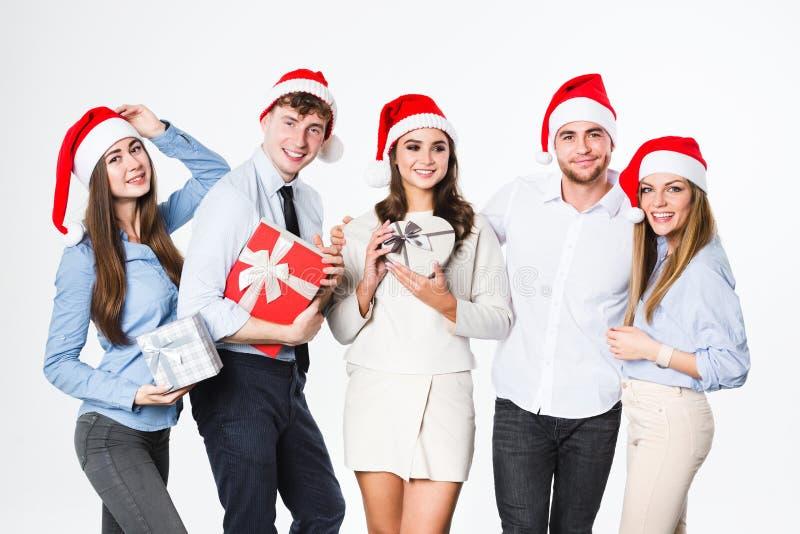 Glückliche Menschen gruppieren in Sankt-Hut mit den Geschenken, die auf weißem Hintergrund lokalisiert werden lizenzfreie stockbilder