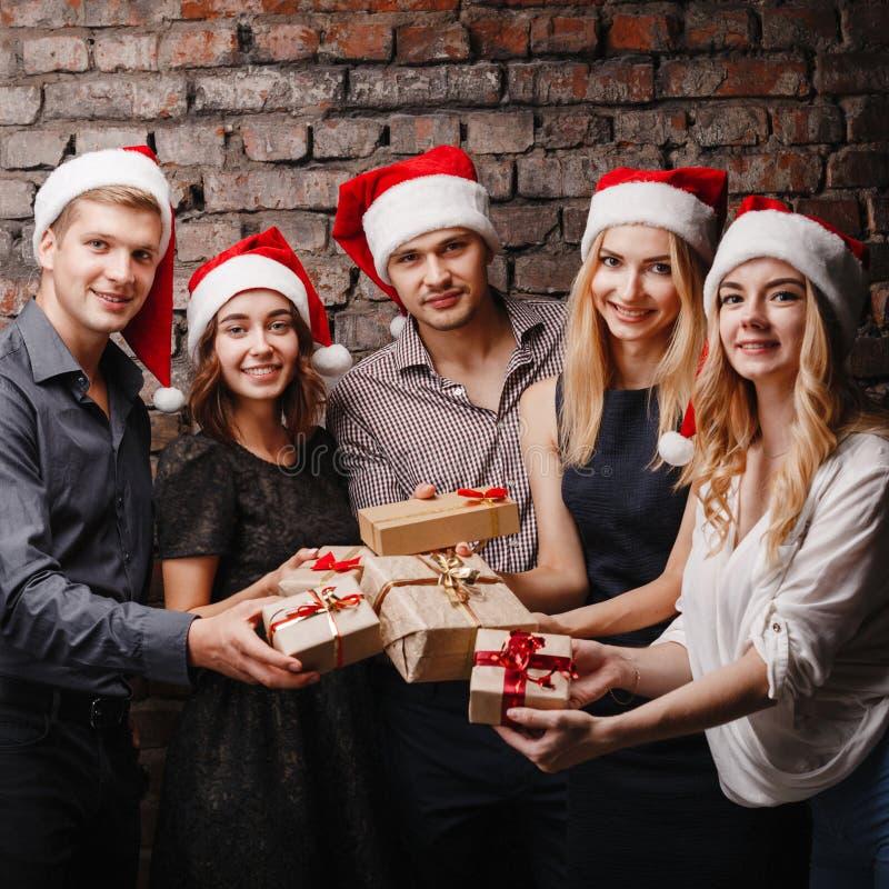 Glückliche Menschen in Sankt-Kappen mit Geschenkboxen lizenzfreies stockfoto