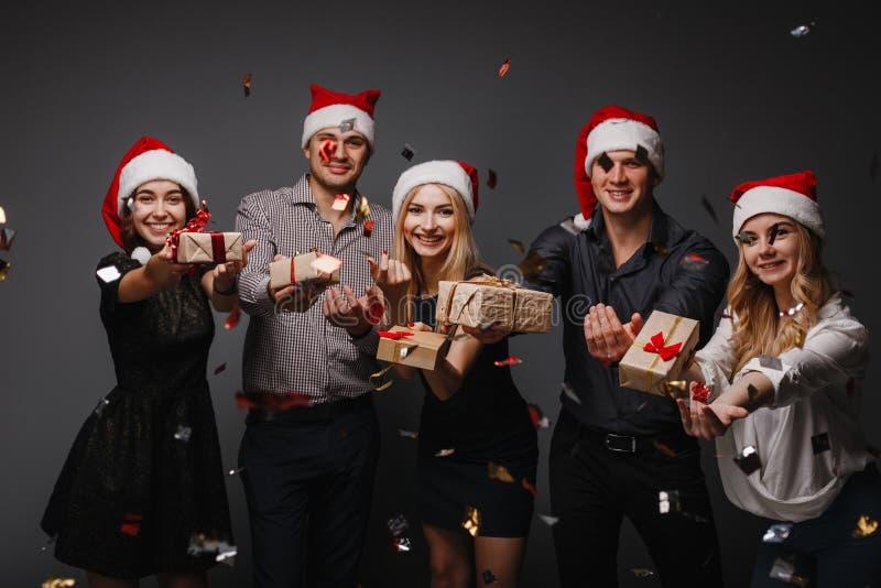 Glückliche Menschen in Sankt-Kappen mit Geschenkboxen lizenzfreie stockfotos