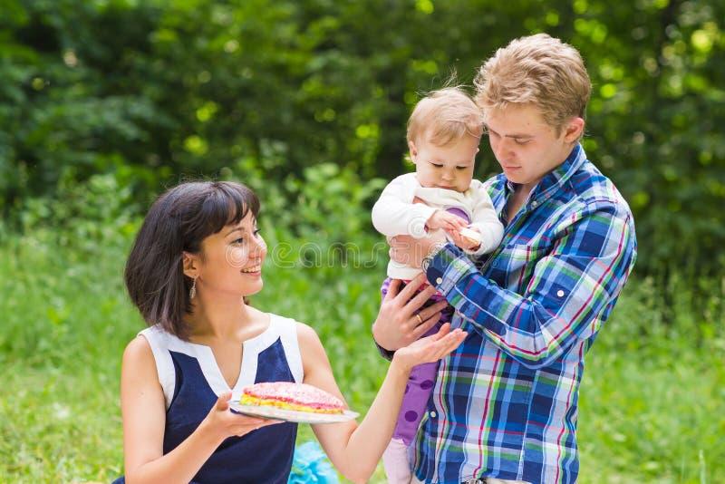 Glückliche Mischrasse-Familie, die ein Picknick hat und im Park spielt lizenzfreie stockfotos