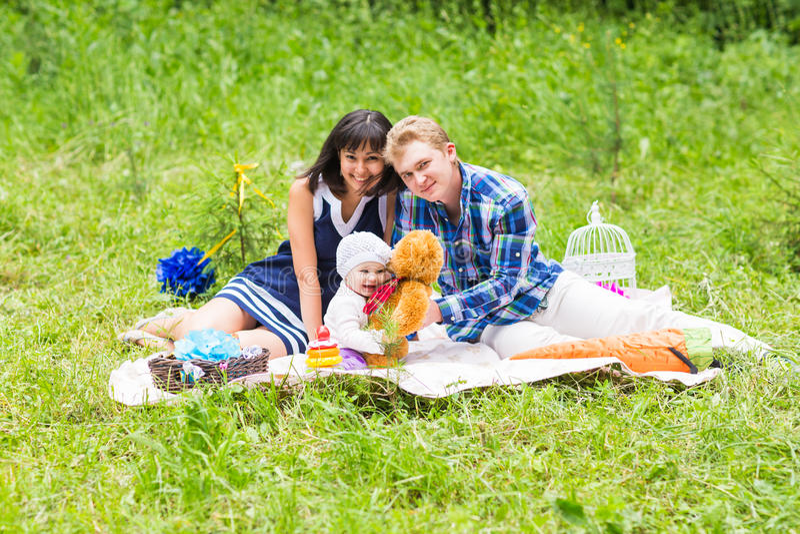 Glückliche Mischrasse-Familie, die ein Picknick hat und im Park spielt stockfotos