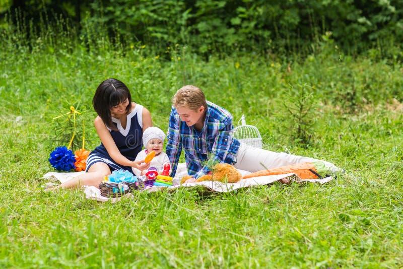 Glückliche Mischrasse-Familie, die ein Picknick hat und im Park spielt stockbild